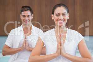 Smiling couple in white sitting in lotus pose with hands togethe