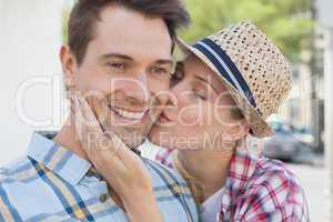 Young hip couple smiling at camera woman kissing mans cheek