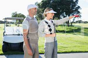 Happy golfing couple looking at course with golf buggy behind