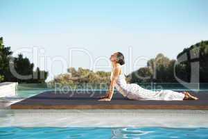 Peaceful brunette in cobra pose poolside