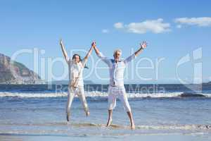 Happy couple jumping up barefoot on the beach