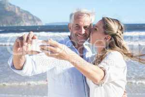 Married couple at the beach together taking a selfie
