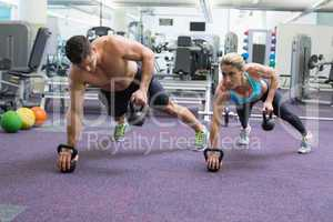 Bodybuilding man and woman lifting kettlebells in plank position