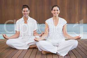 Attractive couple in white sitting in lotus pose smiling at came
