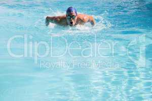 Fit swimmer doing the butterfly stroke in the swimming pool