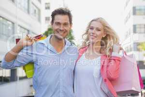 Stylish young couple smiling at camera holding shopping bags