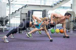 Bodybuilding man and woman holding dumbbells in plank position