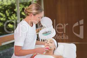 Peaceful brunette getting micro dermabrasion from beauty therapi