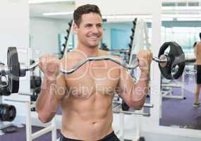 Shirtless smiling bodybuilder lifting heavy barbell weight