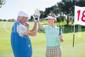 Golfing couple high fiving on the golf course at eighteenth hole