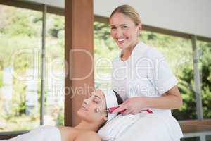 Brunette getting micro dermabrasion with therapist smiling at ca