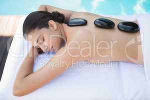 Relaxed brunette lying poolside having a hot stone massage