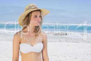 Beautiful blonde on the beach in white bikini and sunhat