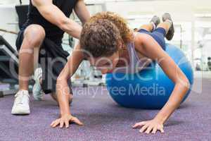 Trainer helping client workout on exercise ball