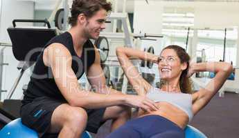 Trainer watching client do sit ups on exercise ball