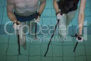 Man and woman holding walking poles in the pool