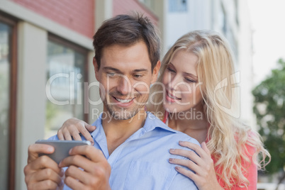 Stylish young couple looking at smartphone
