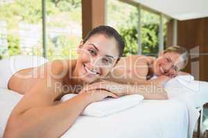 Smiling friends lying on massage tables