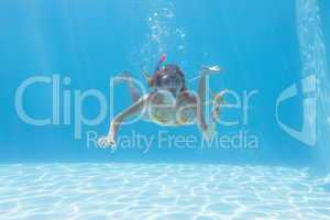 Cute blonde underwater in the swimming pool with snorkel and sta