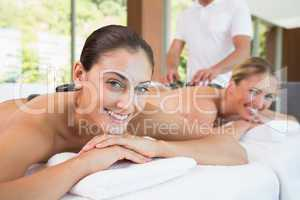 Pretty friends lying on massage tables with hot stones on their