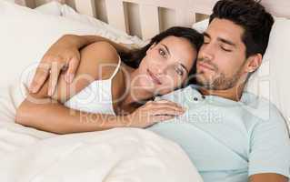 Attractive couple lying in bed smile at camera