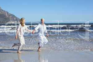 Happy couple skipping barefoot on the beach
