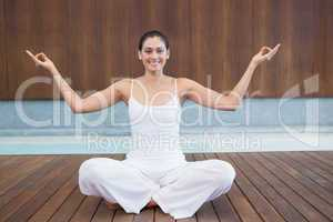 Peaceful happy woman in white sitting in lotus pose