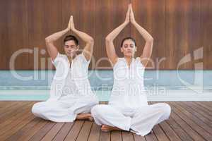 Attractive couple in white sitting in lotus pose with hands toge