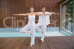 Peaceful couple in white doing yoga together in tree position