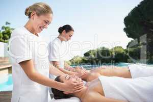 Content couple enjoying head massages poolside