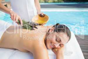 Smiling woman getting an aromatherapy treatment poolside