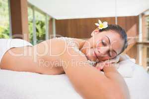 Beautiful brunette lying on massage table with salt scrub on bac