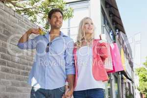Stylish young couple walking with shopping bags