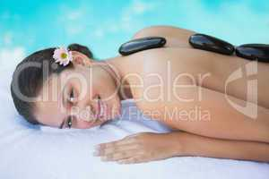Relaxed brunette lying on towel having a hot stone massage