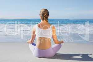 Sporty blonde sitting in lotus pose on the beach