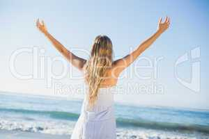 Beautiful blonde in white sundress on the beach