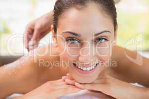 Beauty therapist pouring salt scrub on smiling womans back
