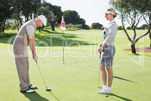 Golfing couple on the putting green at the eighteenth hole