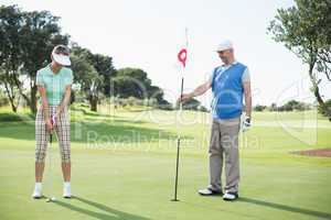 Golfing couple at the eighteenth hole on the golf course