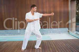 Handsome man in white doing tai chi