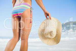 Lower half of fit woman holding sunhat on beach