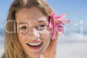 Beautiful happy blonde with flower hair accessory on the beach