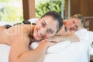 Calm friends lying on massage tables with hot stones on their ba