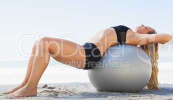 Fit blonde stretching her back on exercise ball at the beach