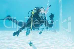 Woman on scuba training submerged in swimming pool making ok sig