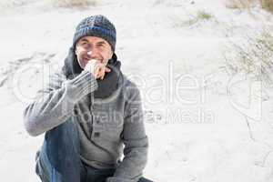 Attractive man thinking on the beach in hat and scarf