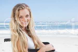 Wheelchair bound blonde smiling at the camera on the beach