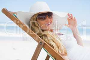 Gorgeous blonde sitting at the beach wearing sunhat and sunglass