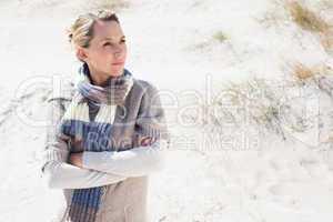 Attractive blonde standing on the beach in woolen scarf