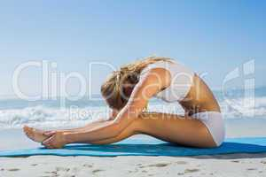 Gorgeous fit blonde in seated forward bend pose on the beach